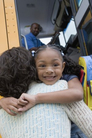 Girl hugging mother over school bus