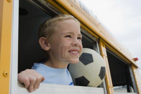 little boy with football in school bus