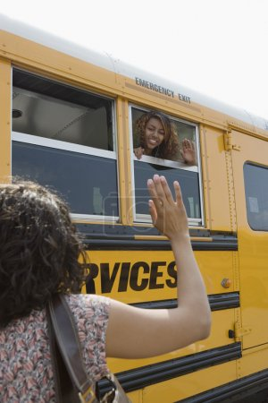 Mother waving to daughter on school bus