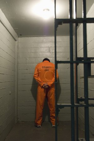 Photo for Prisoner standing against the wall in prison cell - Royalty Free Image