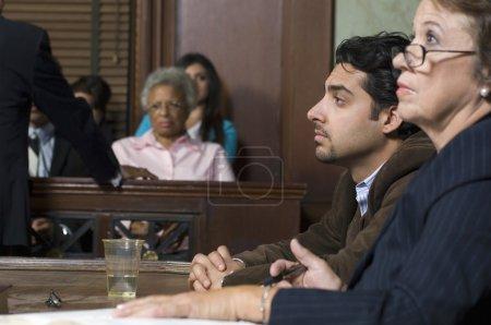 Photo pour Avocat de la défense assis avec le client pendant les poursuites au palais de justice - image libre de droit