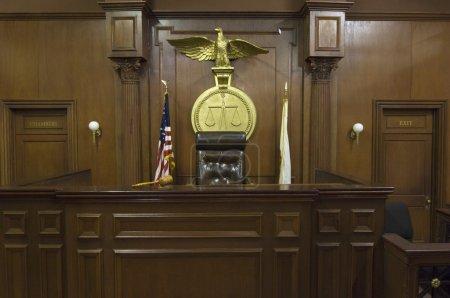 Photo pour Balance juridique avec drapeaux derrière la chaise du juge dans la salle d'audience - image libre de droit