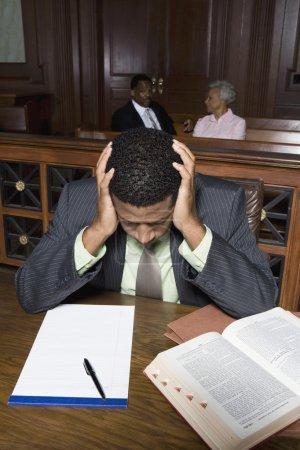 Photo pour Avocat déprimé assis avec un livre de droit et un bloc-notes dans la salle d'audience - image libre de droit