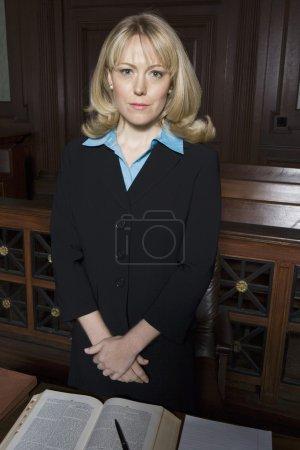 Photo pour Portrait d'une avocate debout à table dans la salle d'audience - image libre de droit