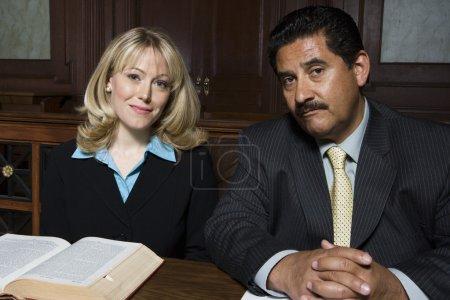 Photo pour Portrait de deux avocats assis ensemble dans la salle d'audience - image libre de droit