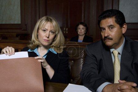 Photo pour Portrait de deux avocats assis dans la salle d'audience - image libre de droit