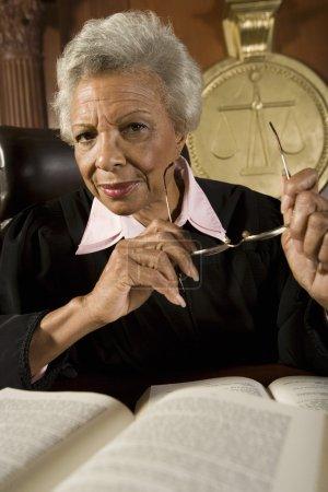 Senior Female Judge Sitting With Books