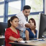 Professor assisting female students in modern high school classroom