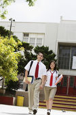 High School Couple Walking in Front of School