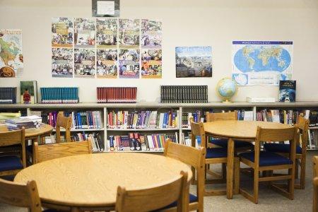 Photo pour Intérieur de la bibliothèque de l'école secondaire avec l'arrangement des étagères, des tables et des chaises - image libre de droit