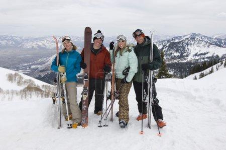 Skiers On Mountain Holding Skis