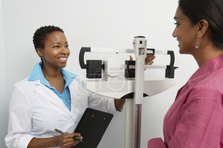 Female Doctor Weighing Patient