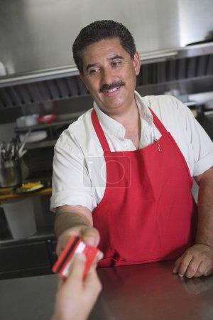 Man Receiving Payment In Restaurant