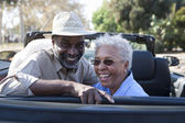 Mature couple at the back seat of car smiling