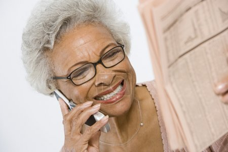 Cheerful Senior Woman Studying Stocks And Shares In Newspaper