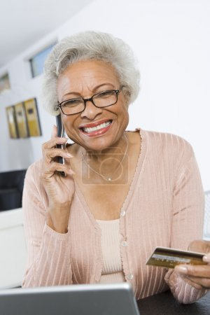 Senior Woman Shopping Online Using Cell Phone And Credit Card