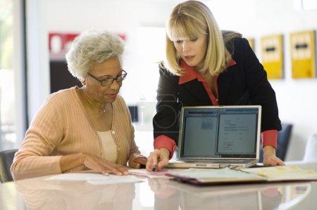 Photo pour Femelle conseiller financier, aider une femme senior afro-américaine à la maison - image libre de droit
