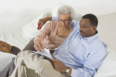 Couple Looking At Bills Worried With Home Finances
