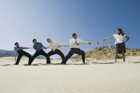 Businessmen Playing Tug Of War Against One Woman