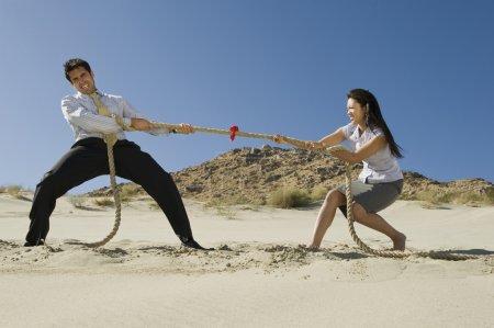 Photo pour Vue latérale de deux entreprises jouant remorqueur de guerre dans le désert - image libre de droit