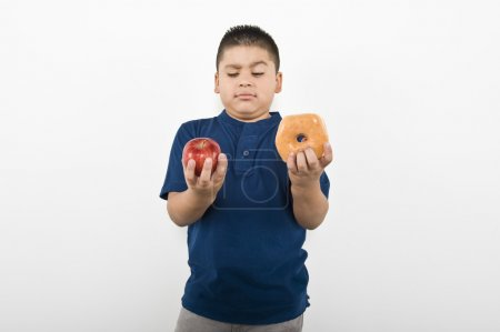 Boy Choosing Between Apple And Doughnut