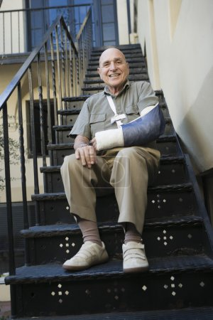 Photo for Portrait of a happy senior man with broken arm sitting on stairs - Royalty Free Image