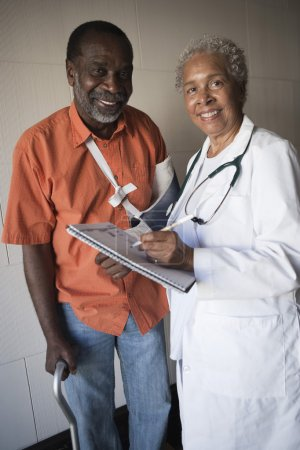 Photo for Portrait of African American female doctor standing with disabled patient in hospital - Royalty Free Image