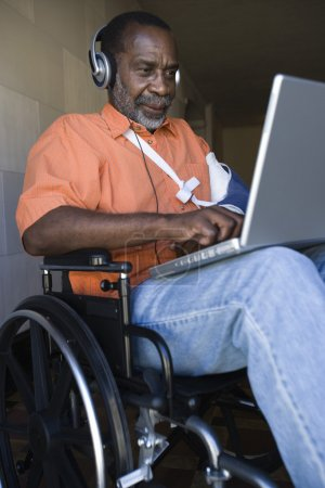 Photo for Injured African American man using laptop and listening music while sitting on wheelchair - Royalty Free Image