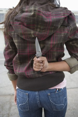 Young Female Criminal Holding Knife