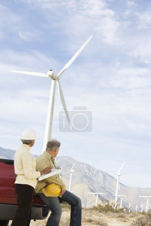 Workers Looking At Wind Farm
