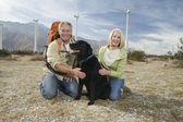 Senior Couple With Dog Near Wind Farm