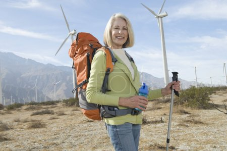 Photo for Portrait of a happy senior woman with hiking pole and backpack at windfarm - Royalty Free Image