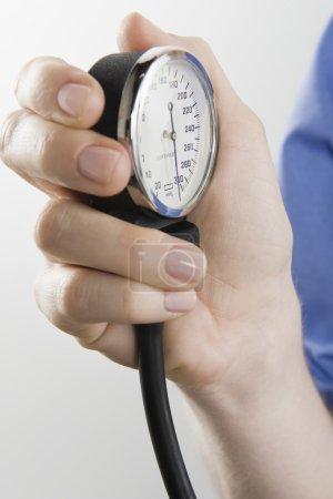 Surgeon's Hand Holding Blood Pressure Gauge