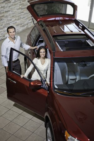 Happy couple in luxury car show room