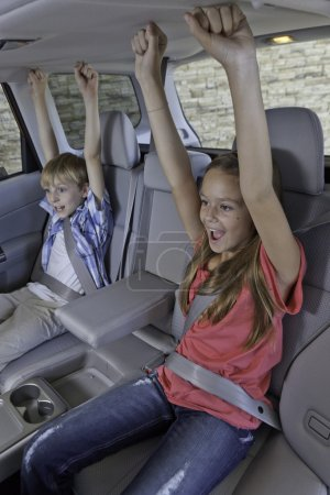 Cheerful children sitting in car