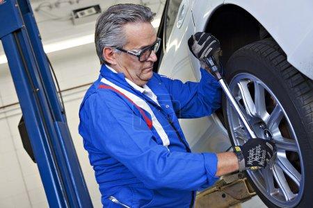Car mechanic with on car tire