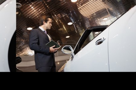 Salesman standing in automobile showroom