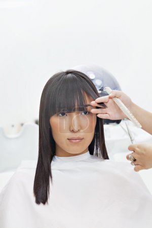 Woman having her hair cut by stylist
