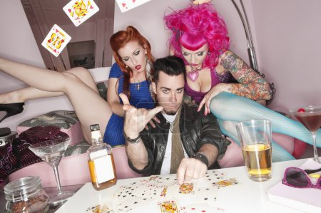 Photo for Man tossing playing cards in air with women sitting besides him - Royalty Free Image