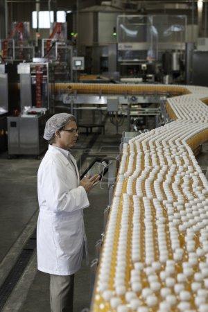 Man inspecting orange juice at plant
