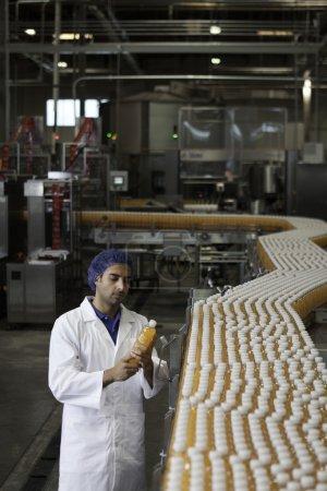 Worker inspecting orange juice