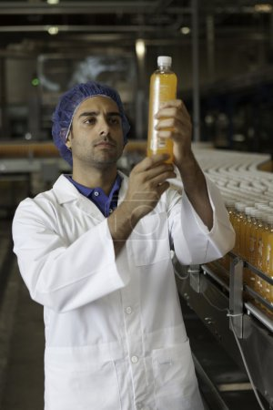 Factory worker with  juice bottle