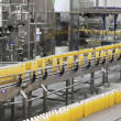 Orange juice bottles on conveyor belt in bottling ...