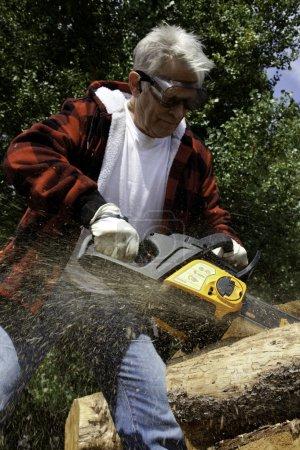 Photo pour Bûcheron senior arbre de coupe senior avec tronçonneuse - image libre de droit