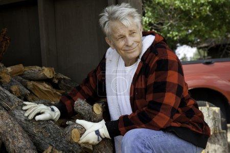 Photo pour Senior homme assis bois de chauffage grumes - image libre de droit