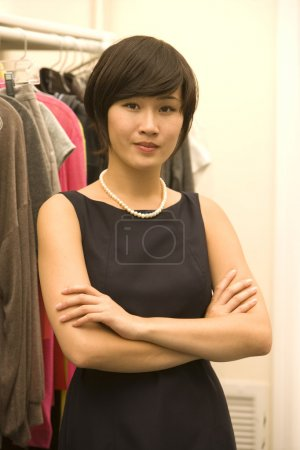 Portrait of confident Asian fashion designer standing with arms crossed