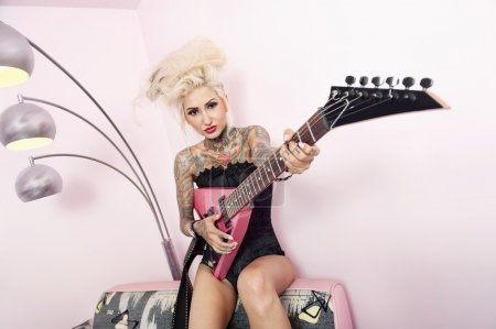 Photo for Portrait of a tattooed woman wearing corset while holding guitar against wall - Royalty Free Image