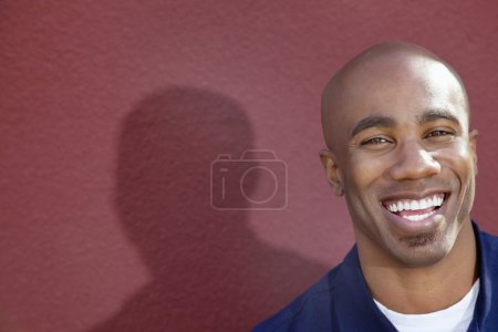 Portrait of a cheerful African American man over colored background