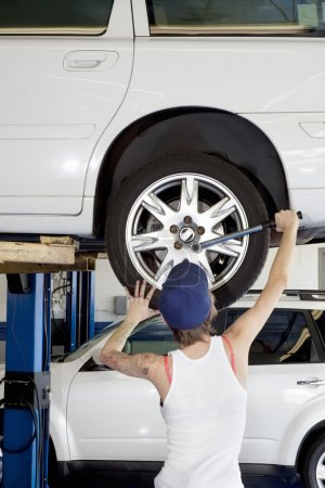 Back view of young female working on car tire in workshop