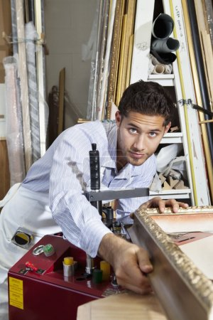 Portrait of a confident craftsman working on picture frame